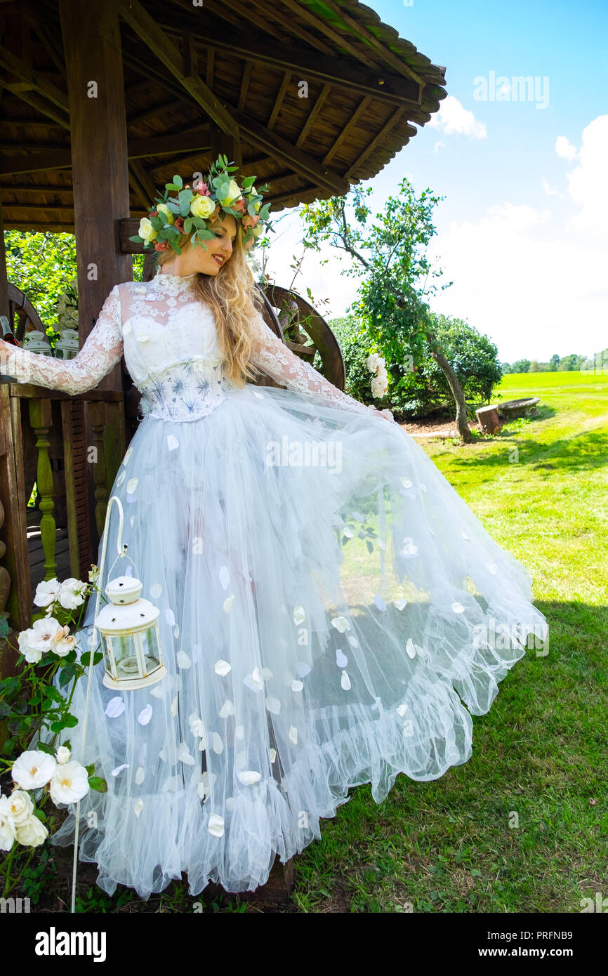 Young girl modelling a full length, designer wedding dress at the festival grounds at Cropredy with floral crown - Stock Image