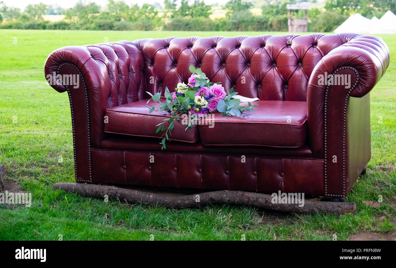 Red leather chesterfield sofa with log to the front, wedding bouquet on the seat and in the centre of a field at Cropredy. - Stock Image