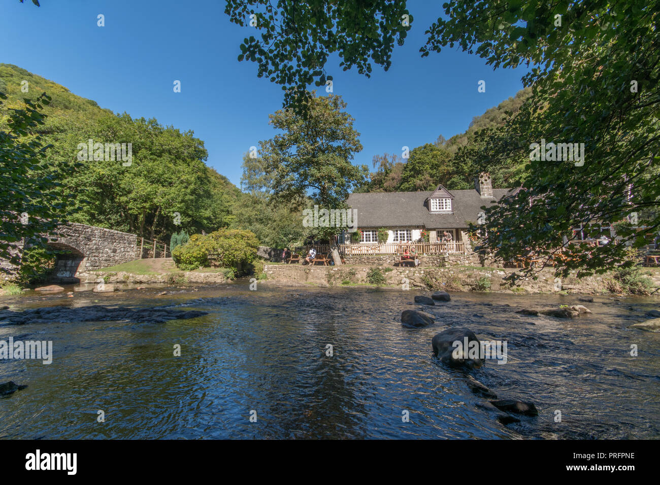 Fingle Bridge Inn next to the river Teign in Dartmoor with people outside eating and drinking - Stock Image