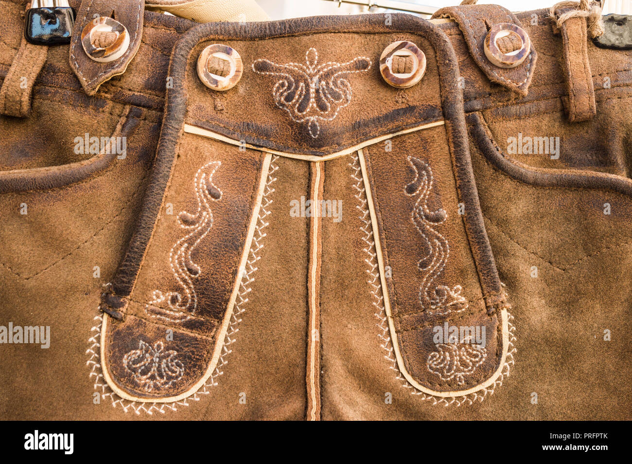Closeup of flap (drop front) of  traditional bavarian and austrian lederhosen (leather pants). Lether relief and embroidered ornament. Decor elements. - Stock Image