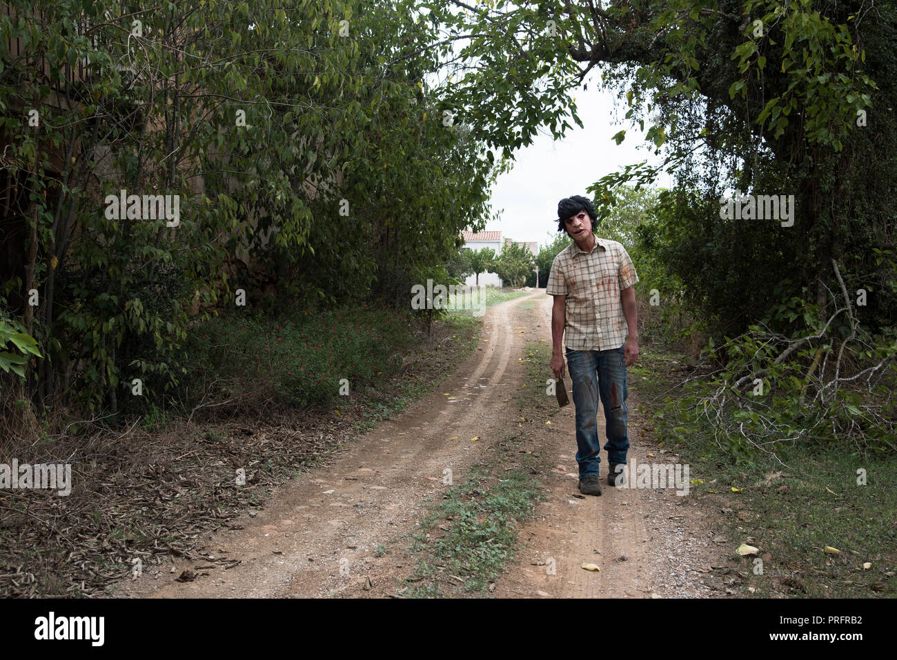 a scary disfigured man, wearing dirty and ragged clothes, with a bloody and rusty meat cleaver in his hand, walking by a dirty road in a disturbing la Stock Photo