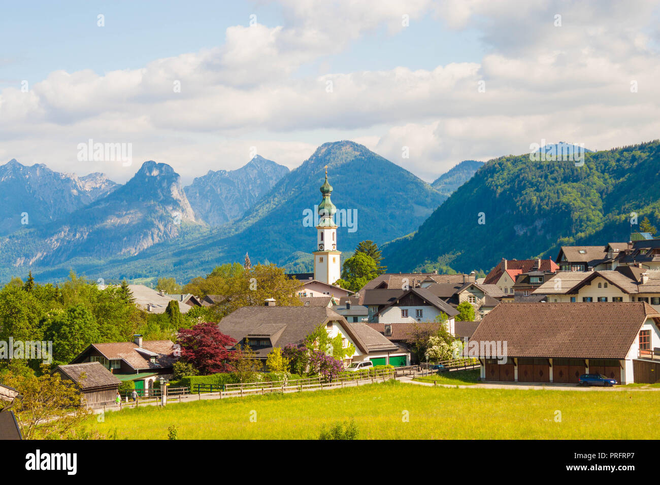 Alpine village St. Gilgen with a church, mountains on background. Summer landscape of countryside, Austria. - Stock Image
