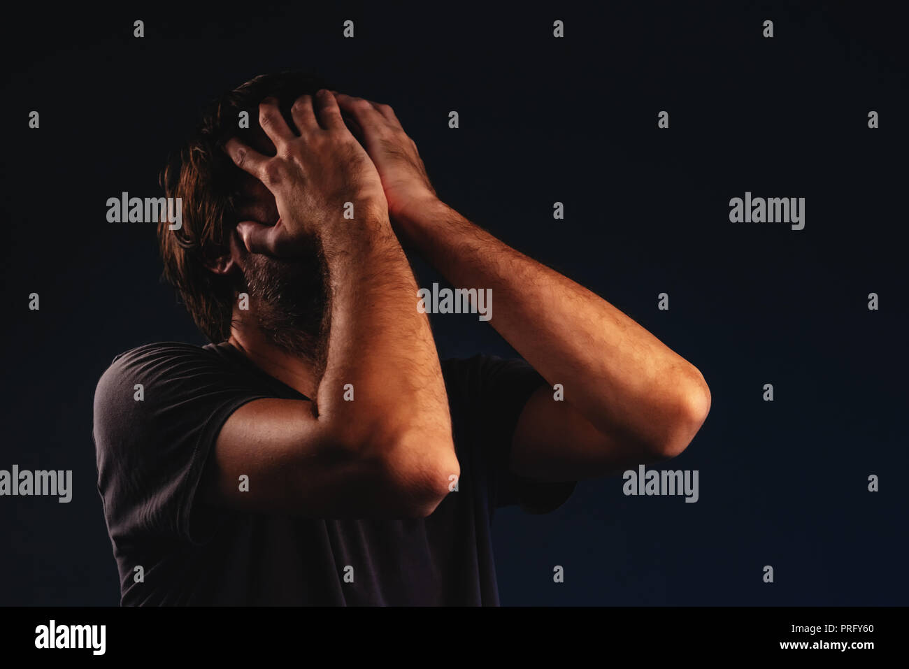 Man is crying in despair, hands covering face, low key portrait - Stock Image