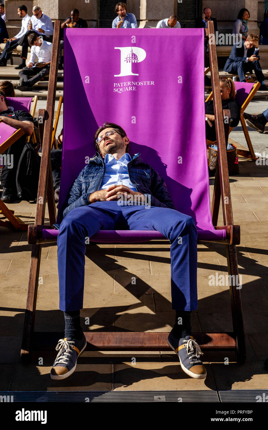 A Young Man Asleep In An Oversized Deck Chair During A Lunch Break, Paternoster Square, London, UK - Stock Image