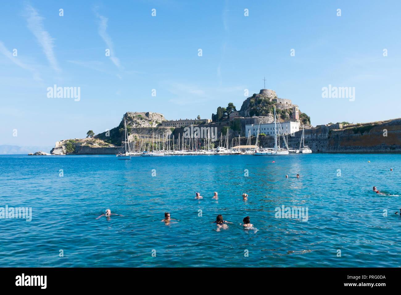 People swimming in the sea near to the Old Venetian Fort in Corfu Town, Corfu, Greece Stock Photo