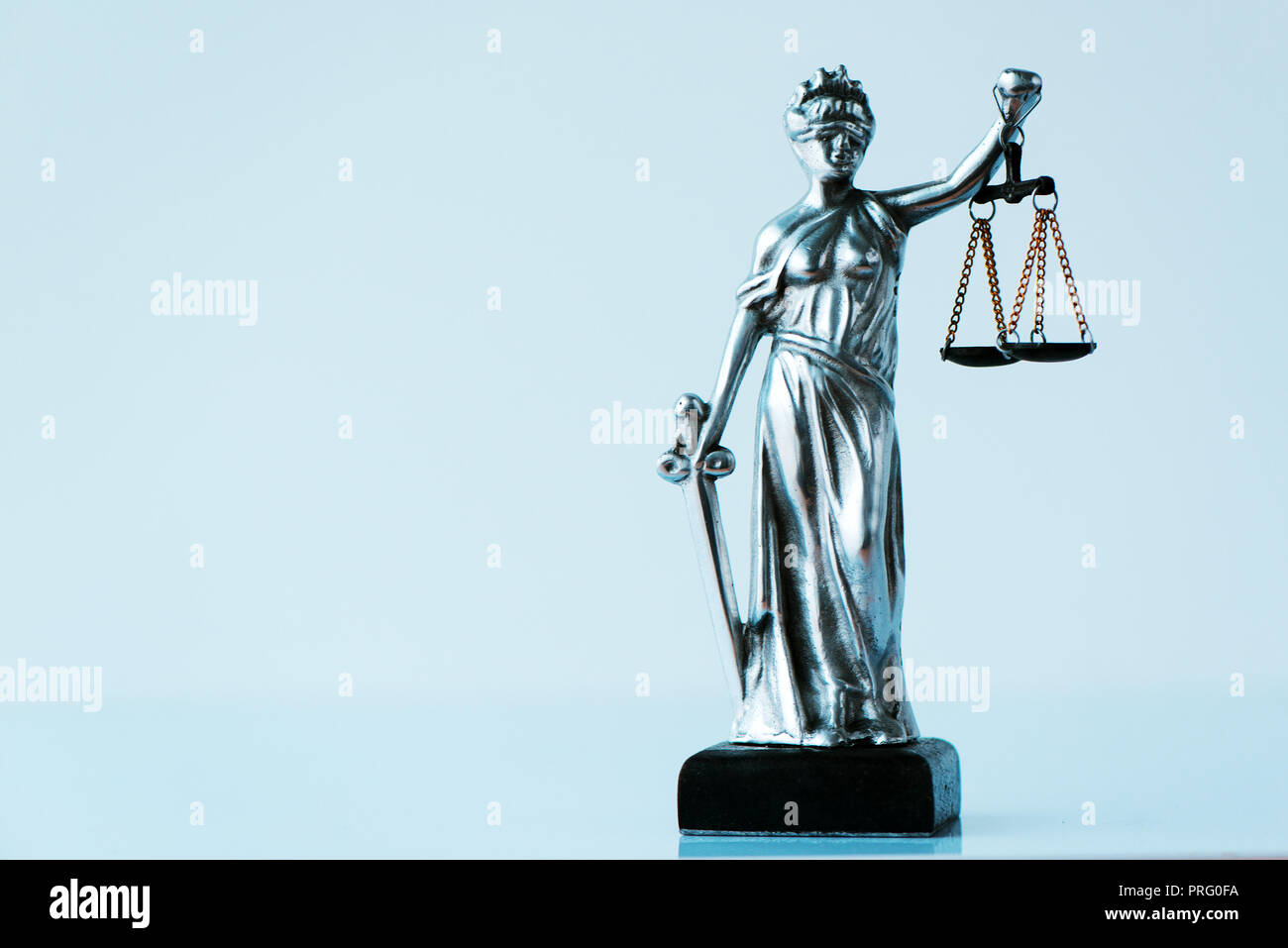 Lady Justice statue in law office. Figurine with blindfold, balance and sword is personification of moral force in judicial system and it's origin is  Stock Photo
