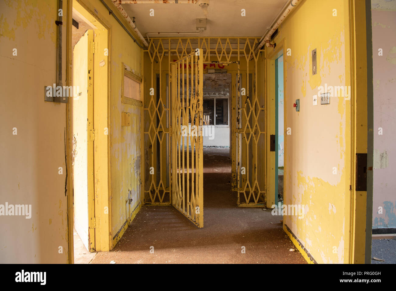 Steel gate at the end of a corridor wing of an abandoned prison. - Stock Image