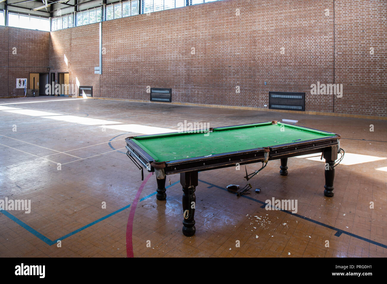 Broken pool snooker table in an abandoned gymnasium. - Stock Image