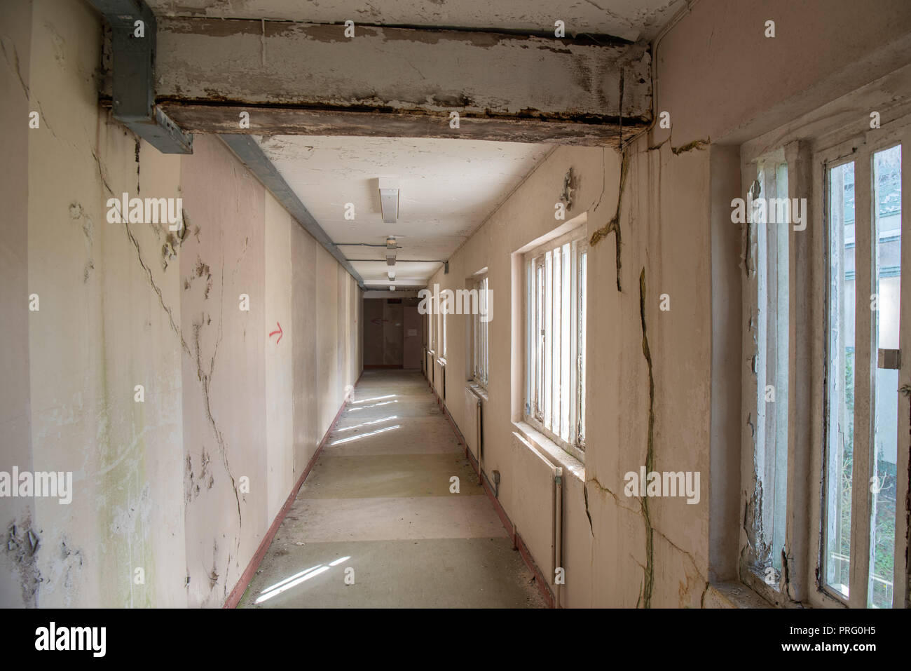 Corridor inside an abandoned prison with windows with steel bars. - Stock Image