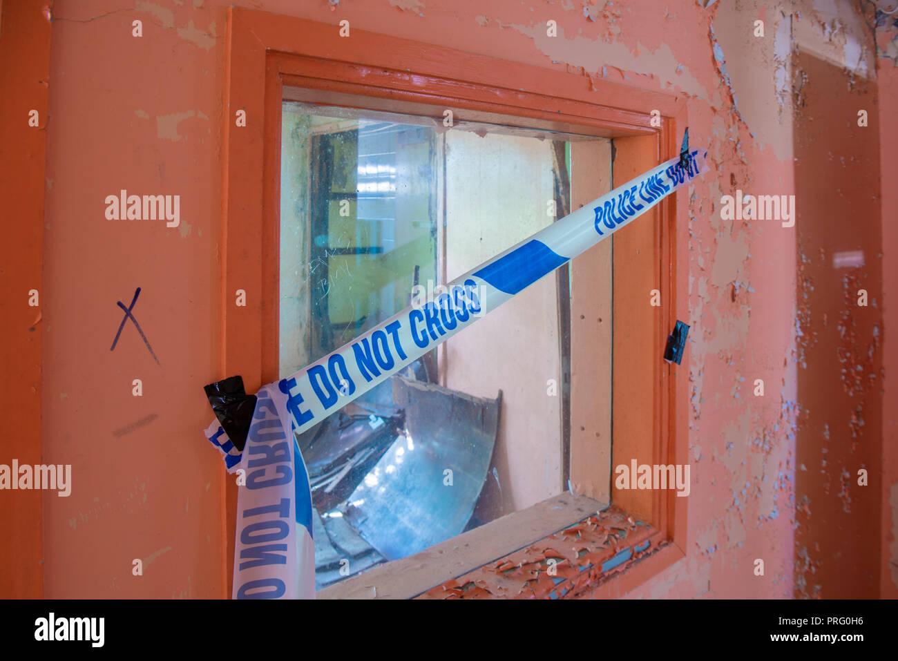 Police cordon tape across a window - Stock Image