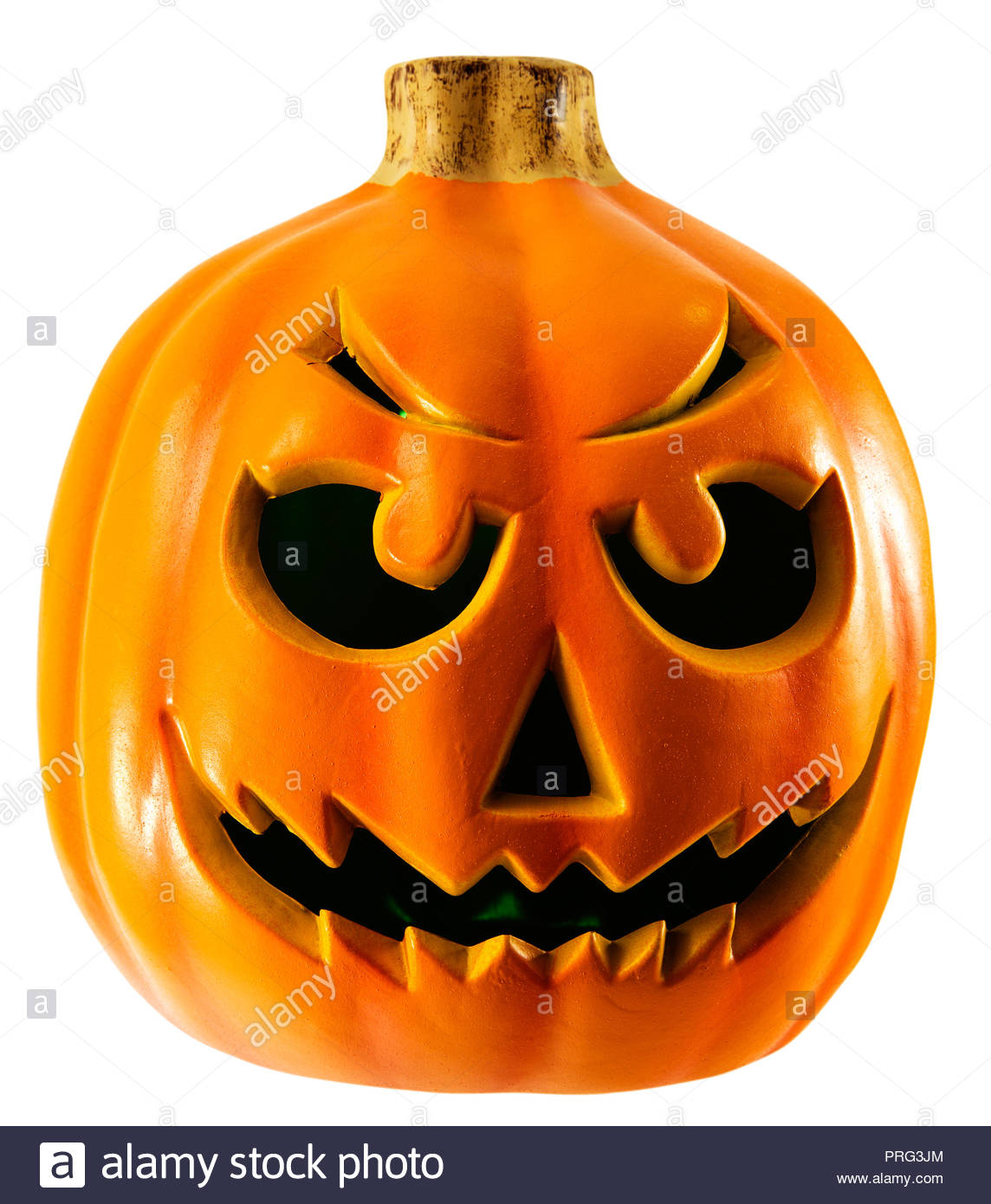 This pumpkin is lit from the interior with a soft green glowing light. Fun menacing grimace for Halloween themes. - Stock Image