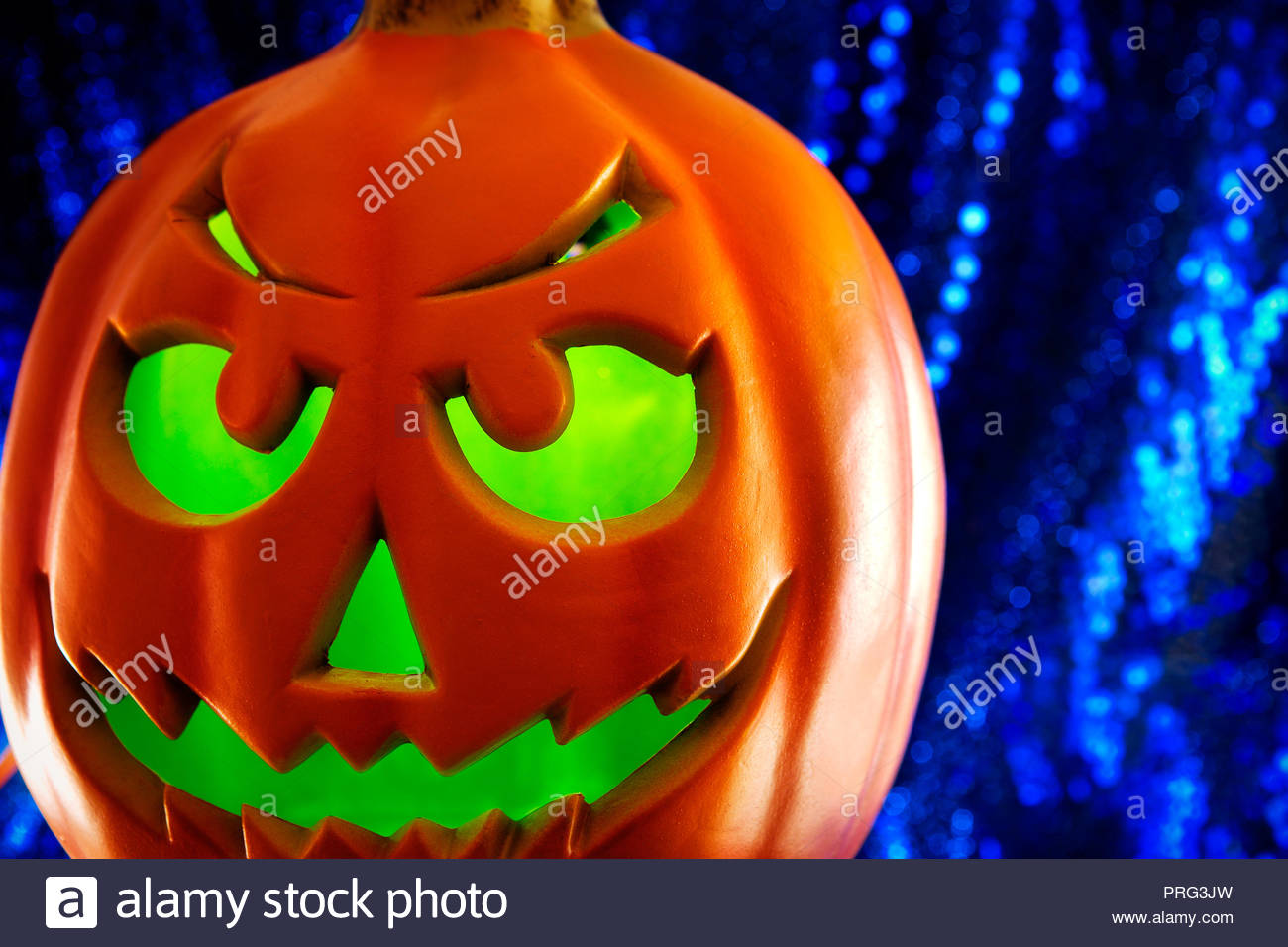pumpkin lit from interior with glowing green light and shimmering