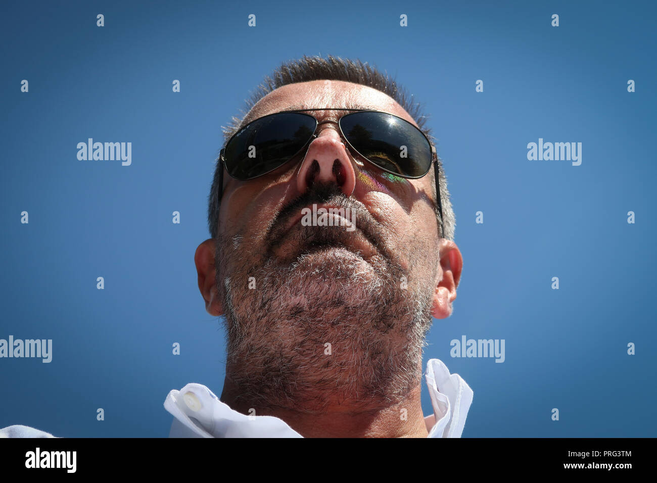 portrait of middle aged man's face with sunglasses and stubble - Stock Image