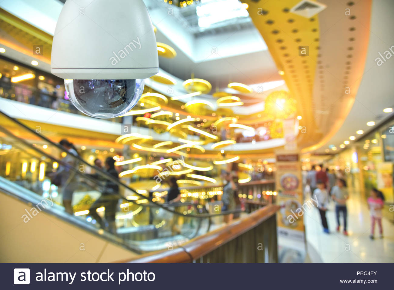 Dome camera and abstract blur background shopping mall interior - Stock Image