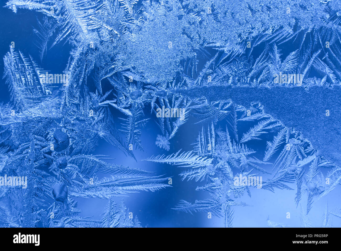 Blue frosty pattern of openwork pointed snowflakes on winter glass pane. - Stock Image
