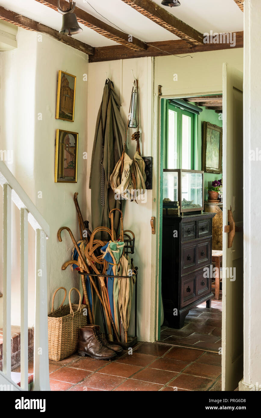 Coats and boots with walking sticks in doorway of cottage, once home to Virgina Wolfe - Stock Image
