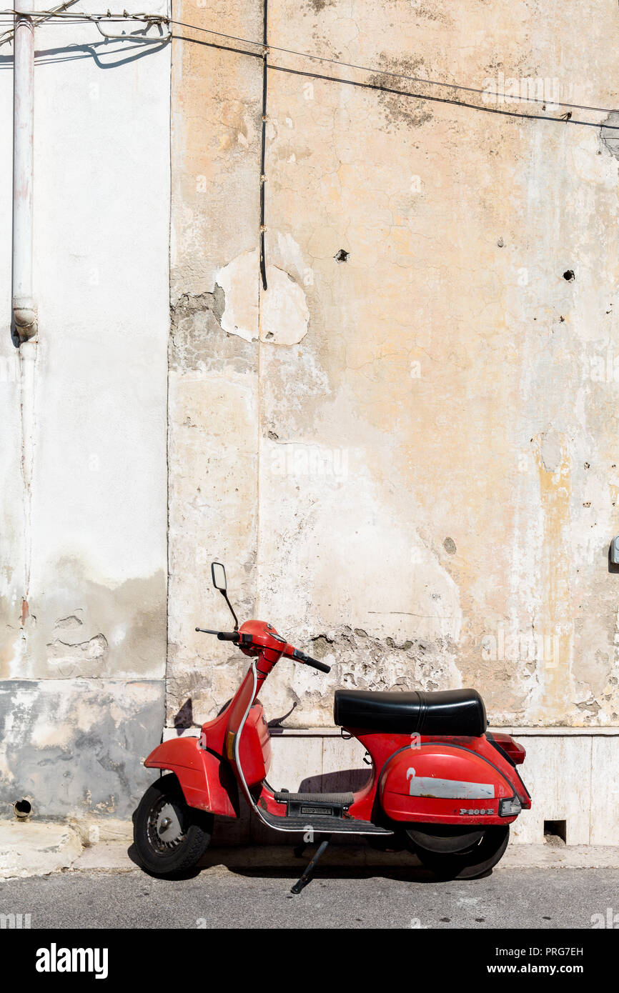 A red scooter against a sandy coloured wall in Procida Island, Bay of Naples, Italy - Stock Image