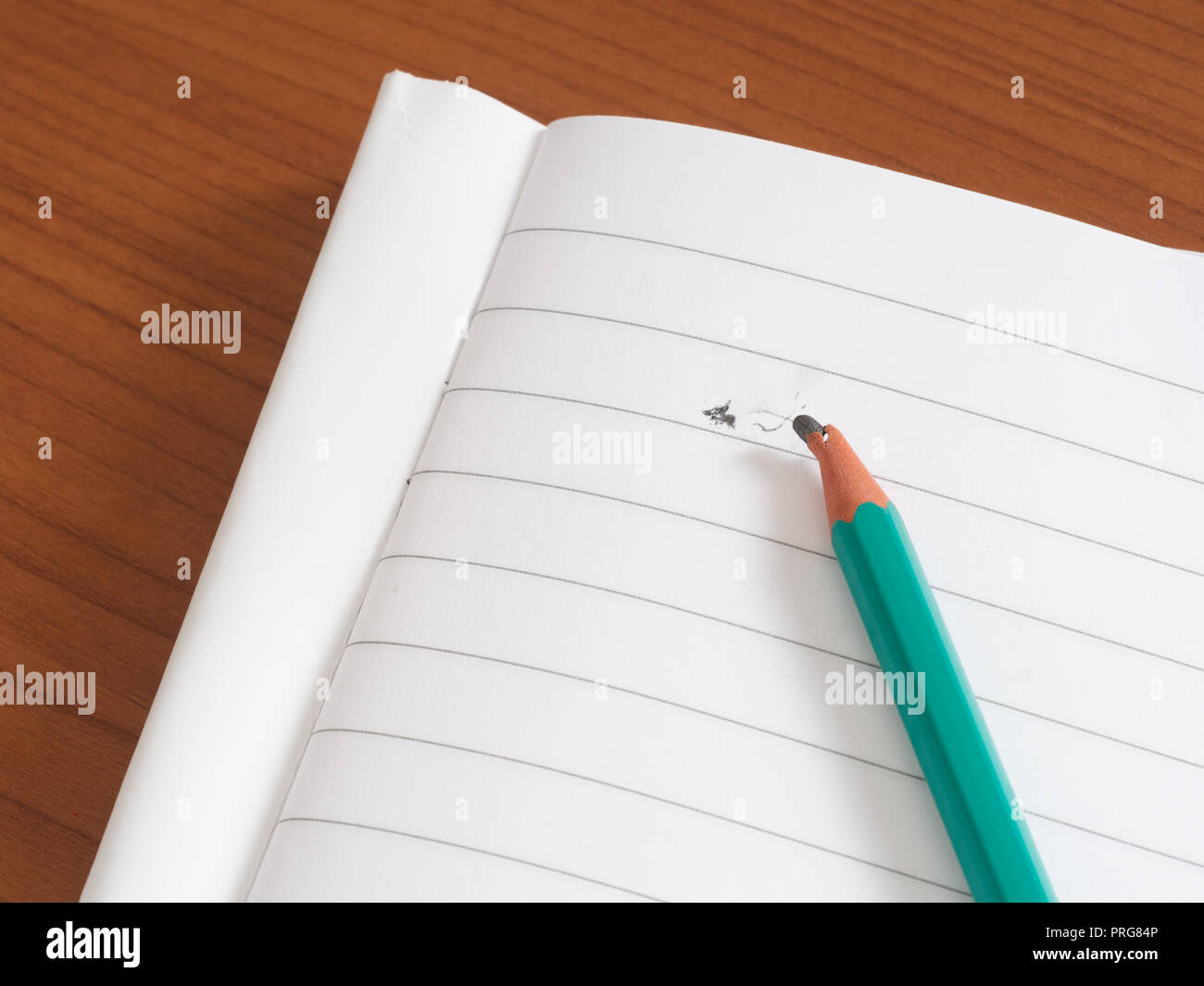 Broken pencil lead on blank lined paper. Stress or writers block. - Stock Image