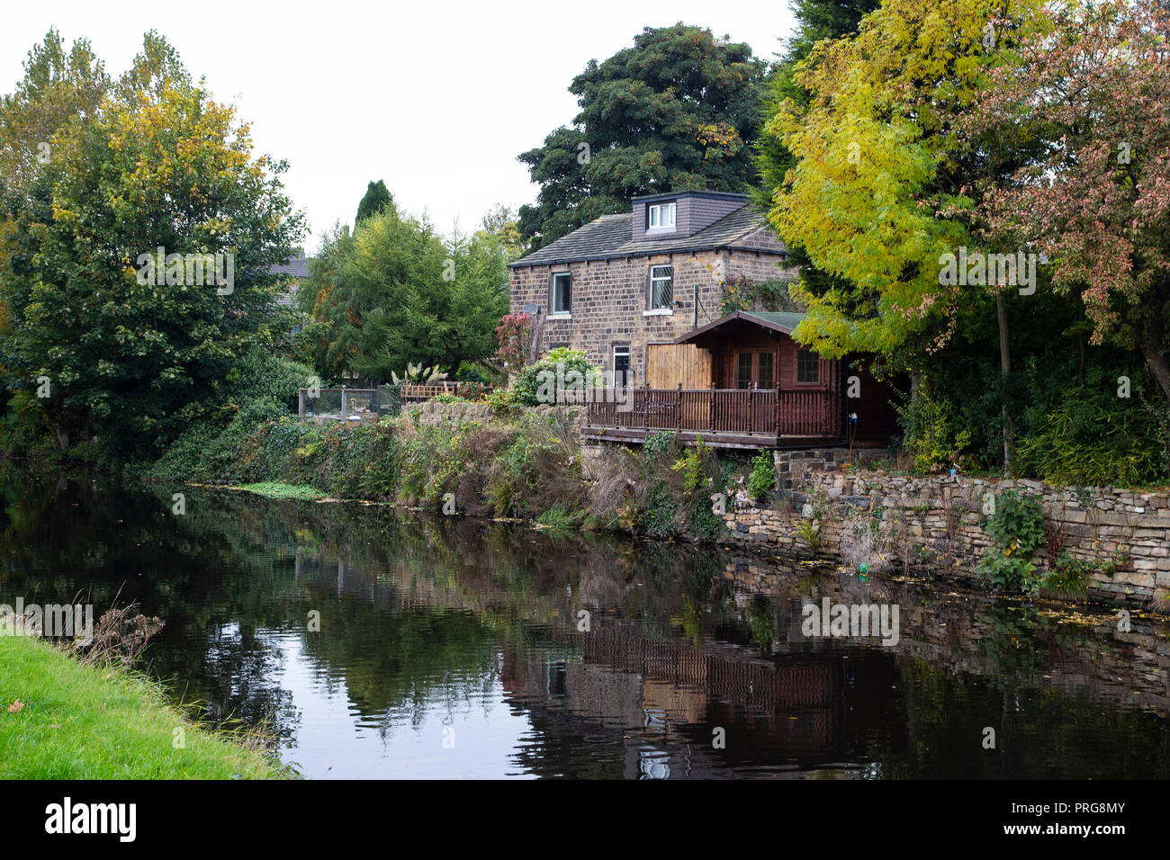 Typical Yorkshire stone built house on the side of the Calder and Hebble canal in Mirfield, West Yorkshire Stock Photo