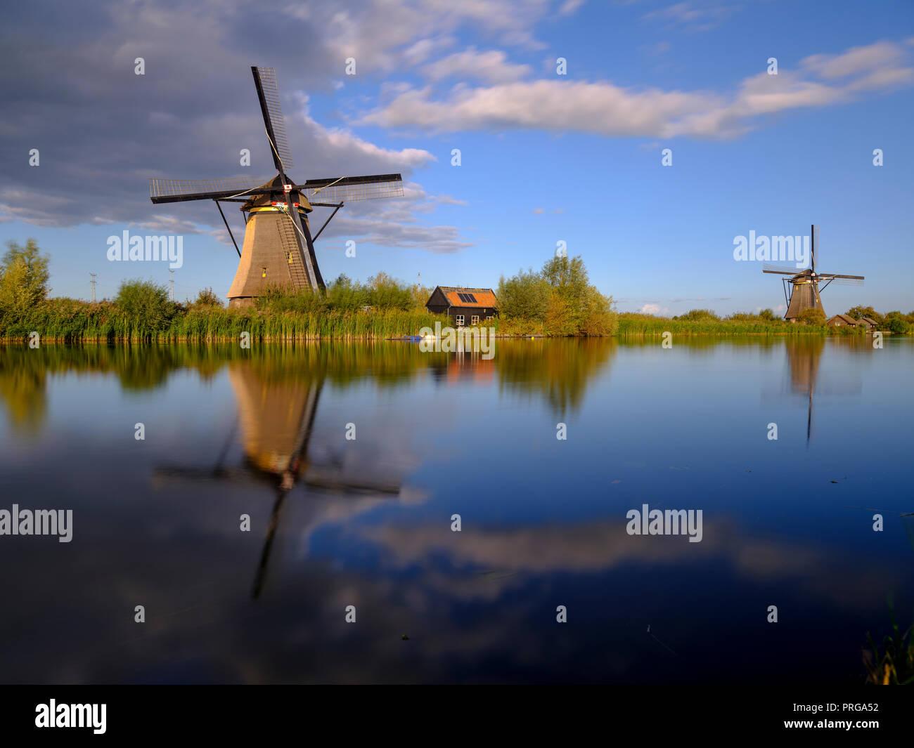 Autumn golden hour light on the windmills, canals and polders of Kinderdijk, near Rotterdam, Netherlands - Stock Image