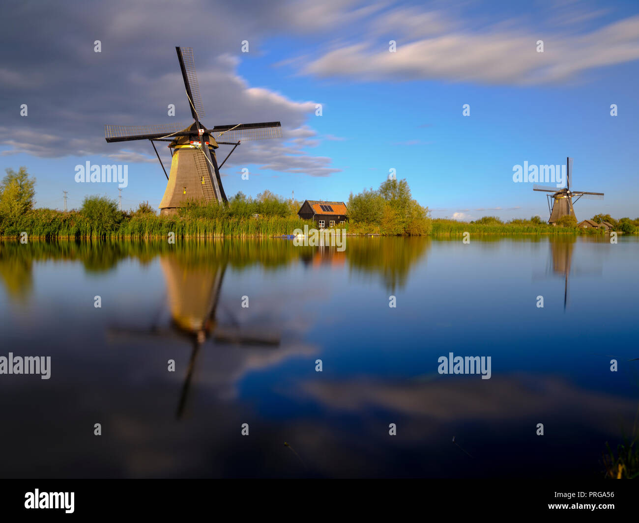 Autumn golden hour light on the windmills, canals and polders of Kinderdijk, near Rotterdam, Netherlands - Stock Image