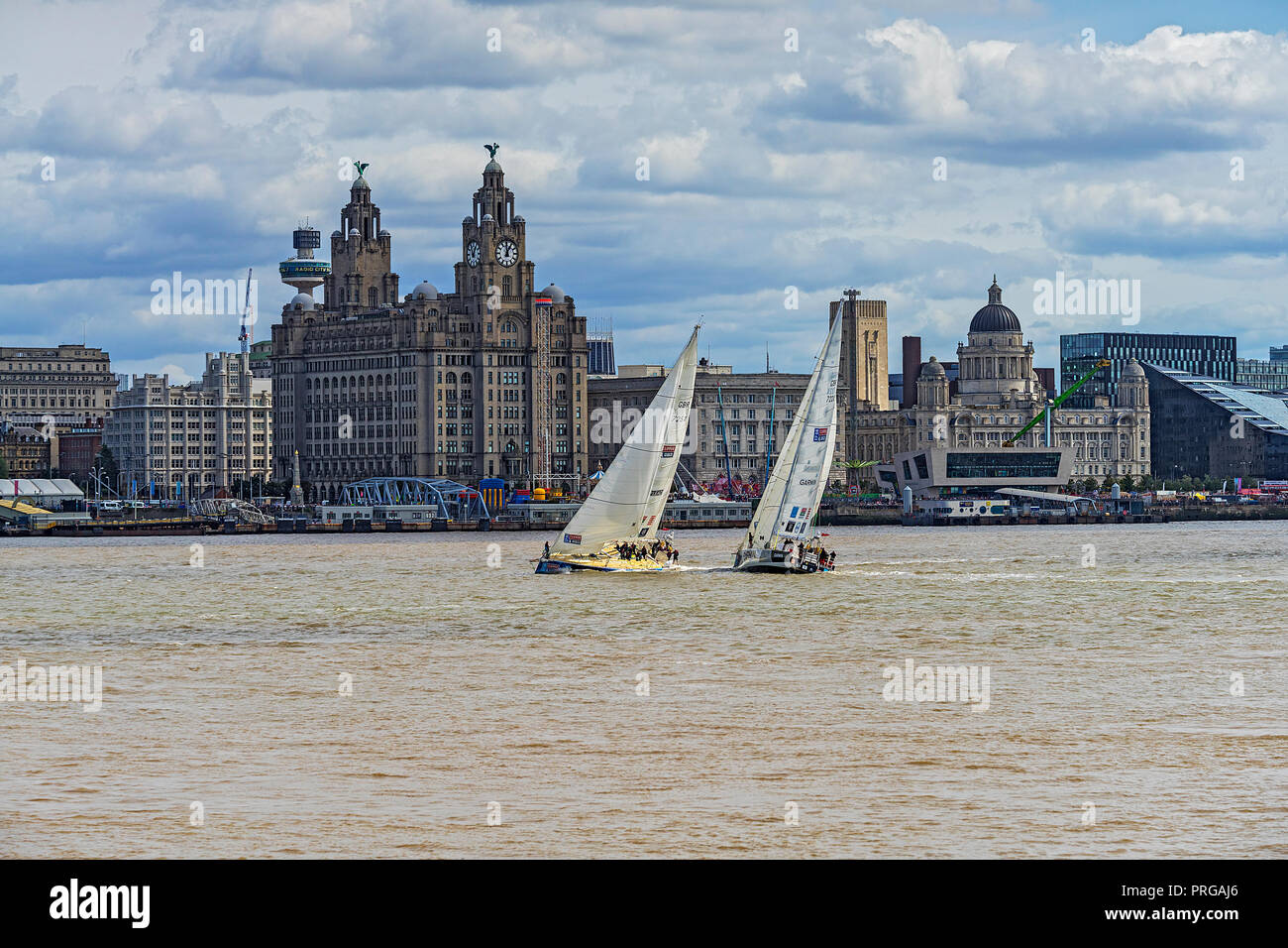 Clipper Round the World Race 2017-18 showing 2 yachts passing the The Three Graces buildings on the Liverpool waterfront on Sunday 20th August 2017 - Stock Image