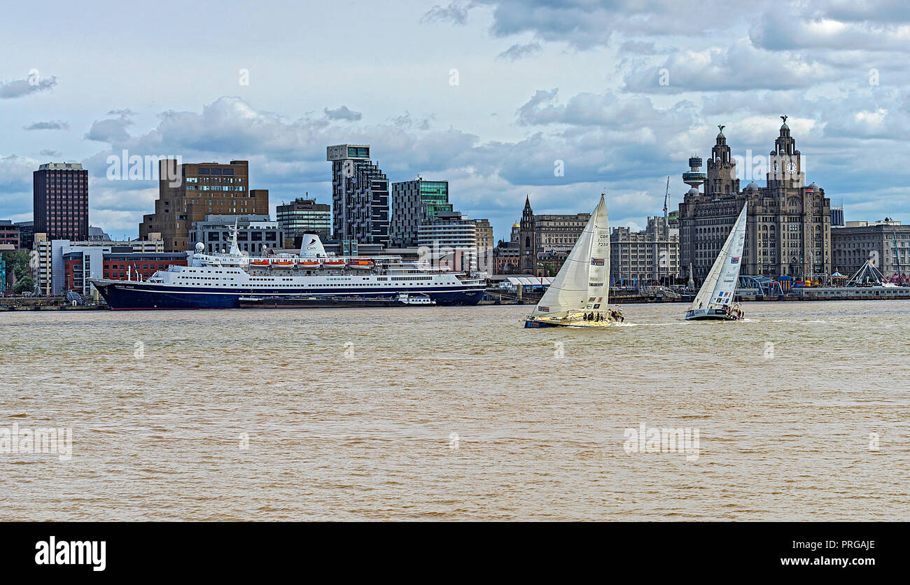 Clipper Round the World Race 2017-18 showing 2 yachts passing the Liverpool waterfront and the Royal Liver Building on Sunday 20th August 2017 - Stock Image