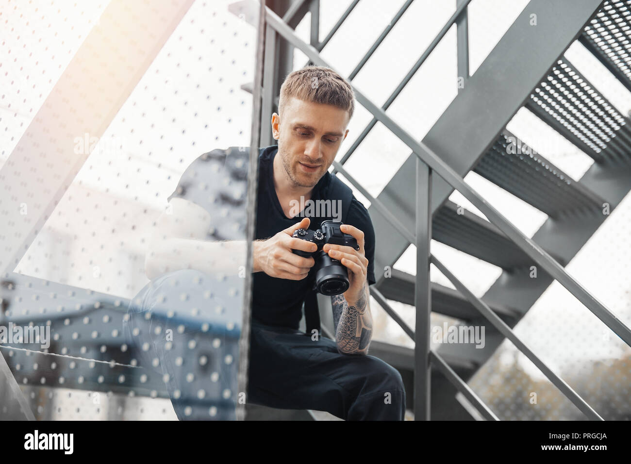 Attractive man sitting at staircase and checking photos in camera. - Stock Image