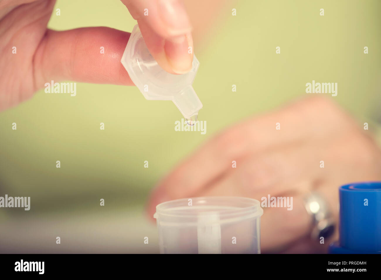 Female hand puts drug in a nebuliser container Close up. Selective focus - Stock Image