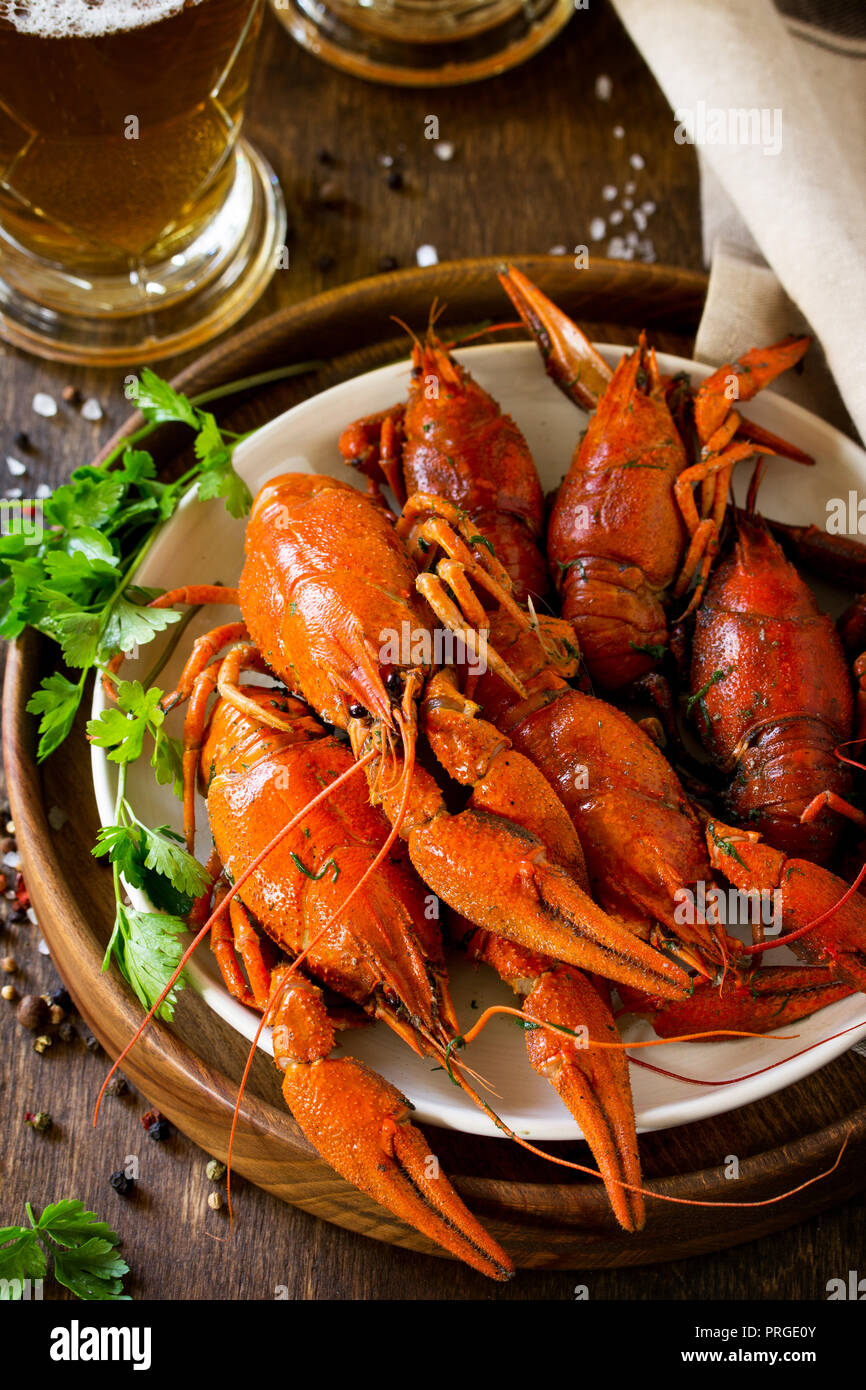 Boiled Crawfish and Fresh Beer in Beakers on a wooden table. Appetizer protein. Stock Photo