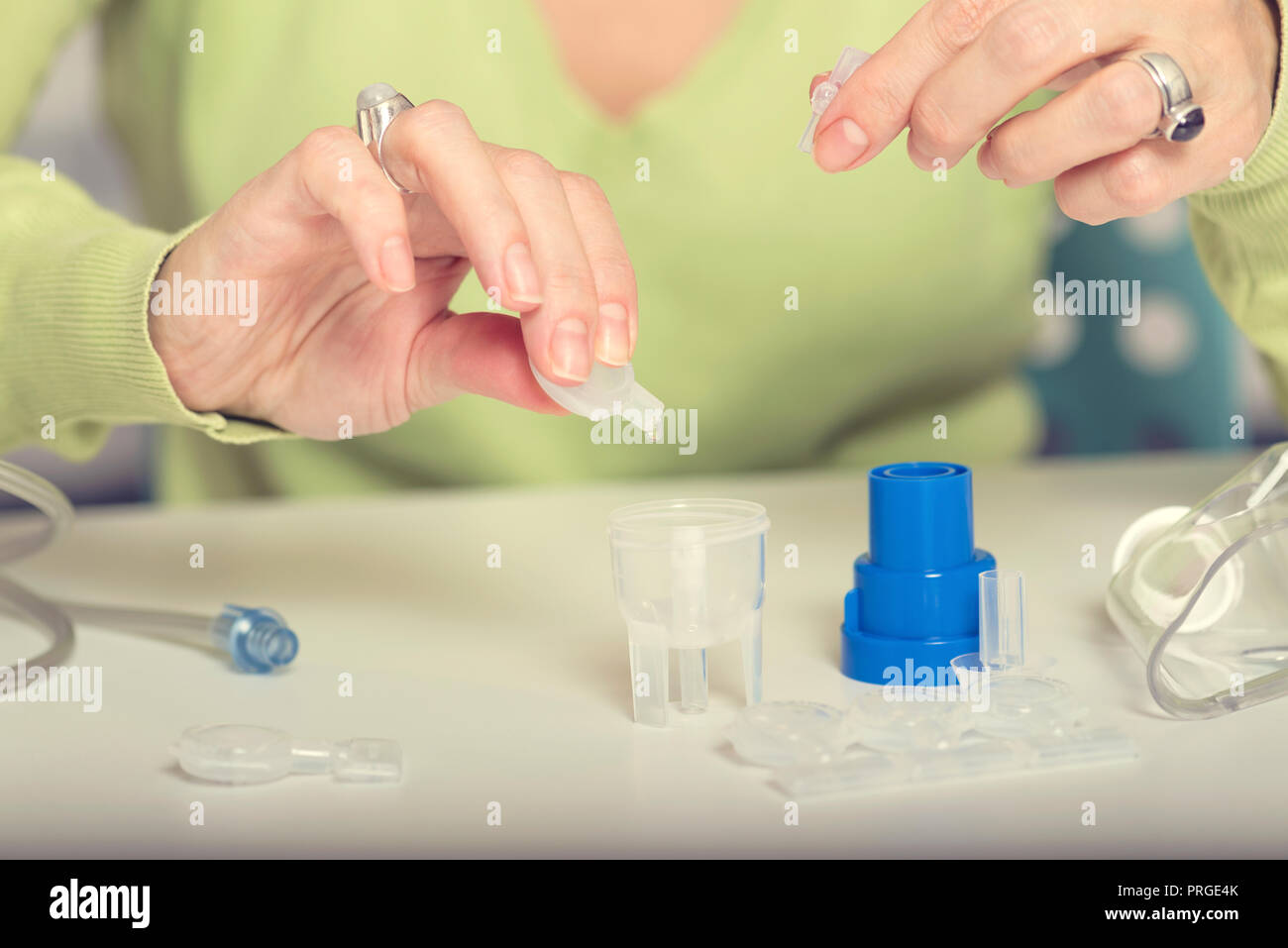 Female hands put drug in a nebuliser container. Selective focus - Stock Image
