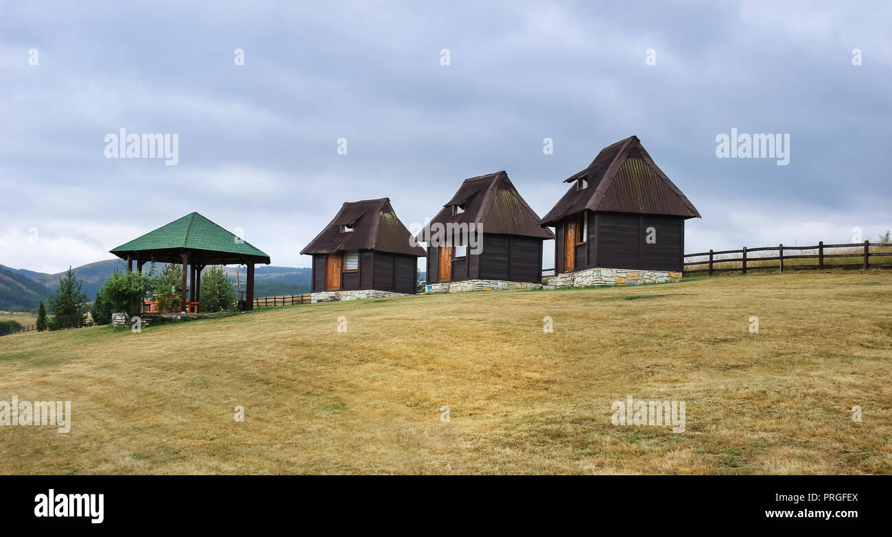 Three traditional little, wooden huts and a summer house in Jokino Vrelo, Serbia, near Zlatibor mountain - Stock Image