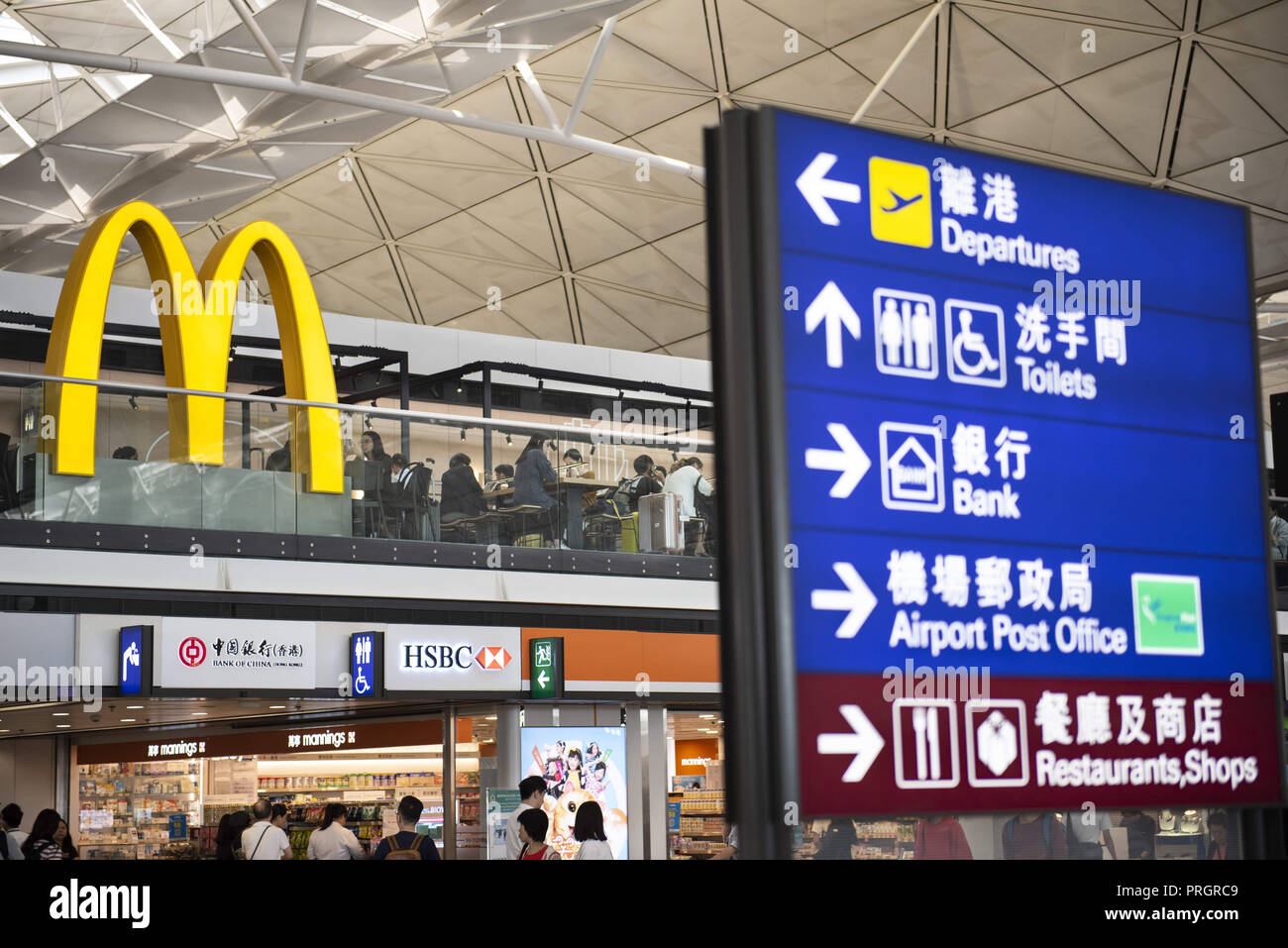 Chek Lap Kok island, Hong Kong. 28th Sep, 2018. At the back, a large McDonald's restaurant logo is seen and at the front, a sign post at Hong Kong terminal 1 airport giving direction where the departure hall, toilets, police office are located Credit: Miguel Candela/SOPA Images/ZUMA Wire/Alamy Live News - Stock Image