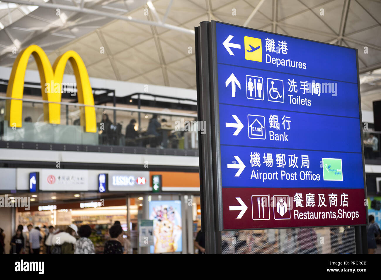 Chek Lap Kok island, Hong Kong. 28th Sep, 2018. A sign post is seen at Hong Kong terminal 1 airport giving direction where the departure hall, toilets, police office are located. At the back, a large McDonald's restaurant logo sign is visible. Credit: Miguel Candela/SOPA Images/ZUMA Wire/Alamy Live News - Stock Image