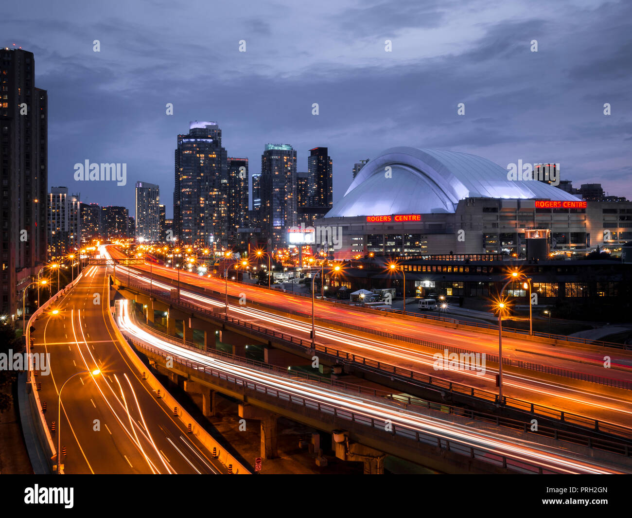 Toronto's Rogers Center dome from Gardiner Expressway with light trains showing movement of traffic on road with buildings in the backdrop - Stock Image