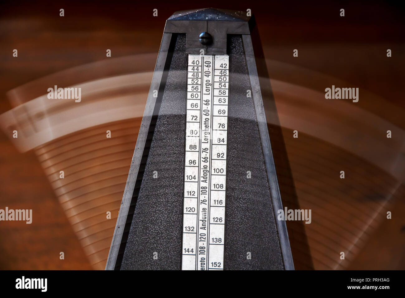 Close up of a vintage metronome with swinging pendulum - Stock Image