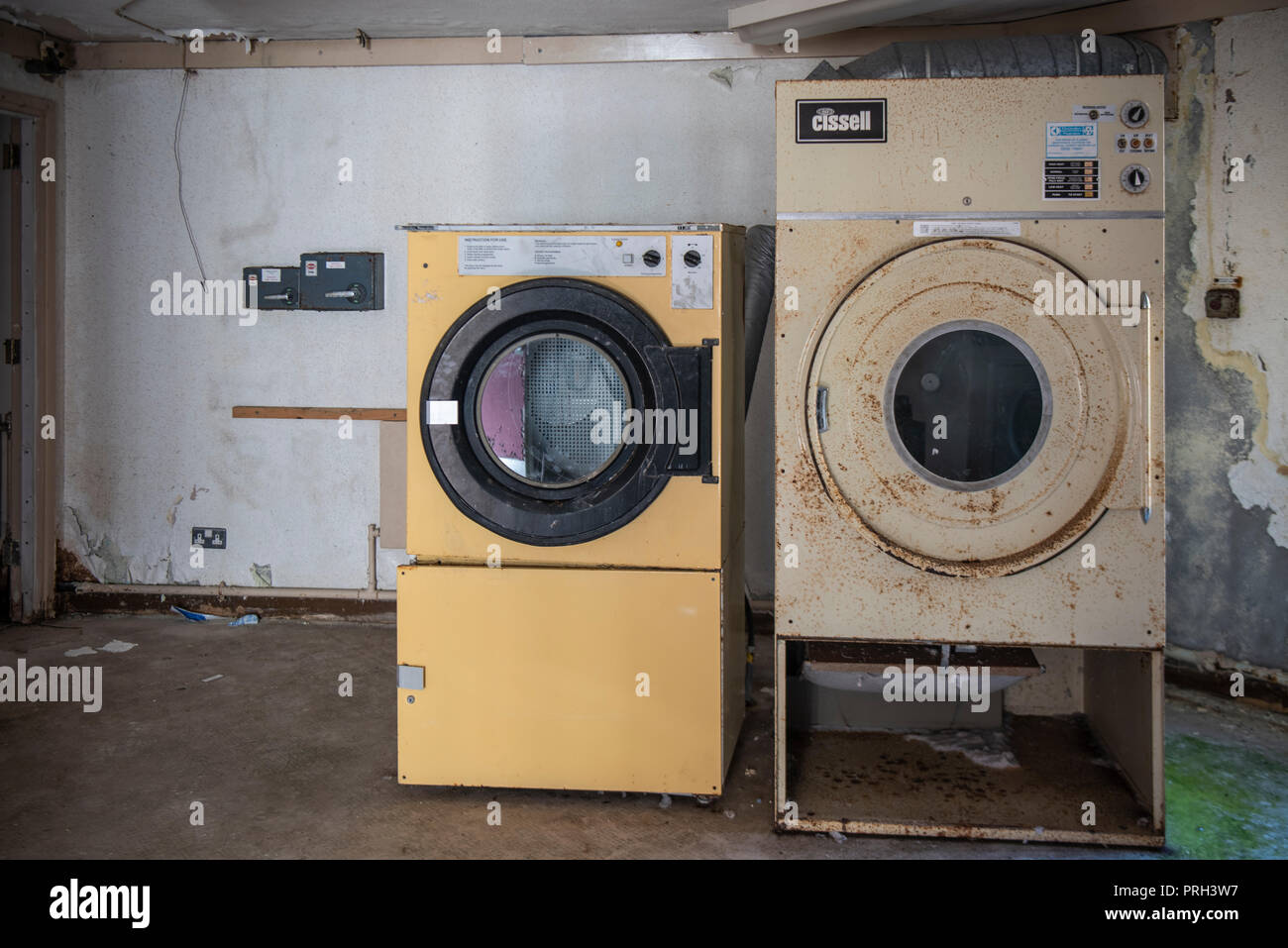 Industrial tumble drier and washing machine in an abandoned building. - Stock Image