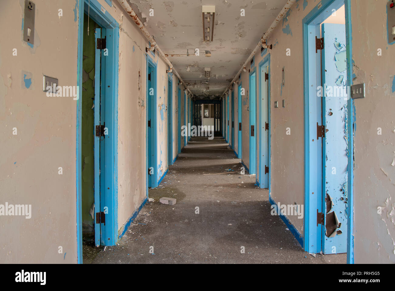 Corridor of prison cell doors inside an abandoned prison. - Stock Image