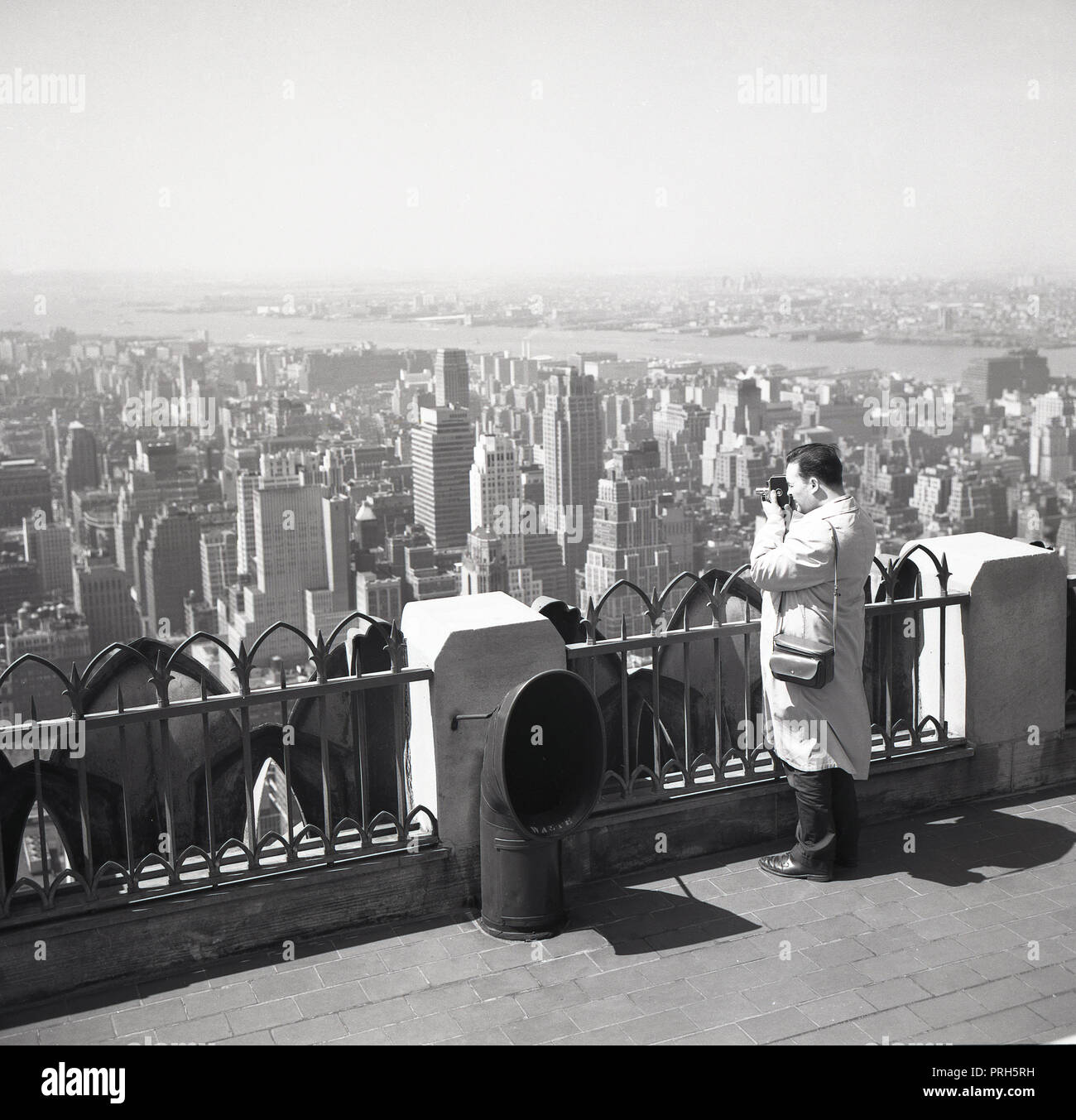 1950s, historical, man using a cine film camera to film the skyline and views of New York city from the top of the Empire State building, New York, NY, USA. - Stock Image