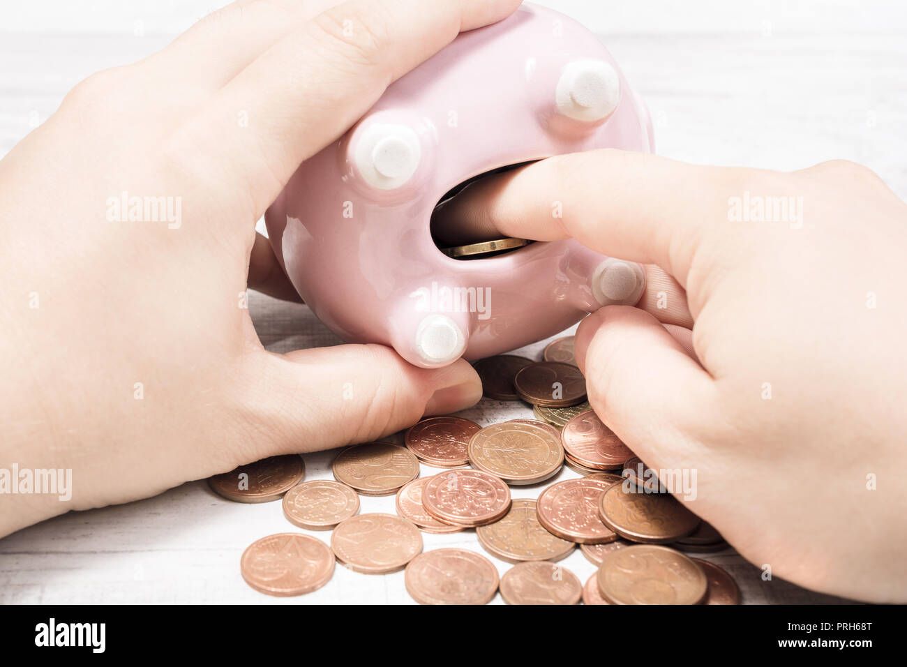 Hand Collecting Coins Out Of Open Piggybank - Stock Image