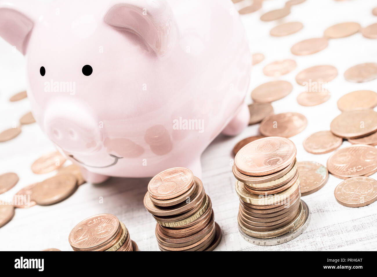 Pink Piggybank Surrounded By Coins And Piles Of Euros - Stock Image