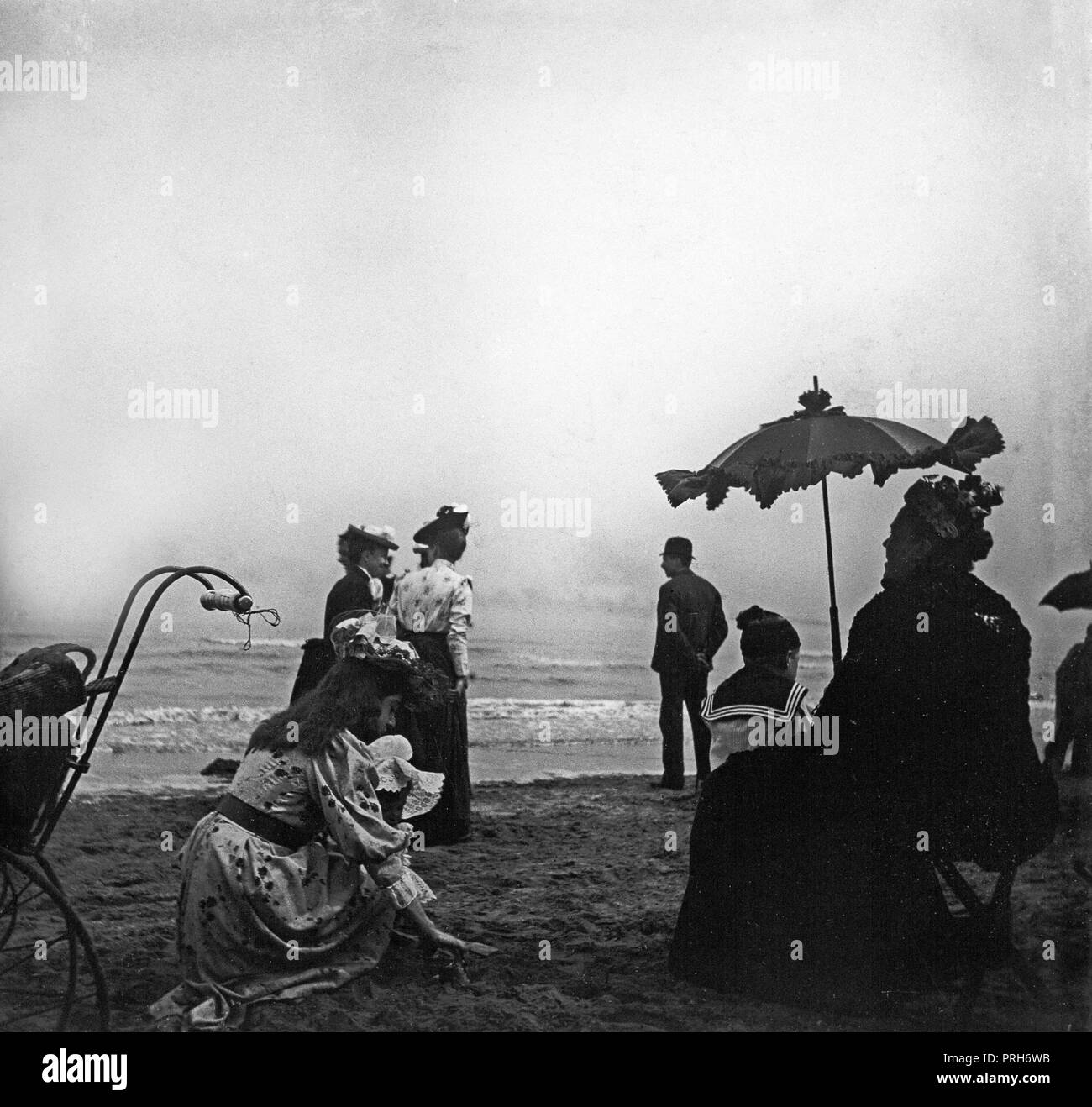A late Victorian photograph showing groups of people at the a seaside resort in England. An elderly lady sheltering beneath a parasol, whilst a young girl attends to a small child. - Stock Image