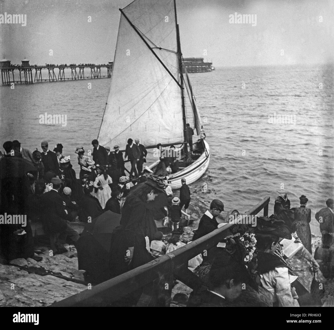 A late Victorian photograph showing groups of people, some disembarking from a small boat, and with a pier in the background, at the a seaside resort in England. - Stock Image