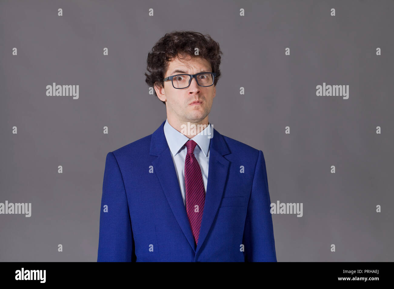 Young boy with glasses and blue suit grimacing - Stock Image
