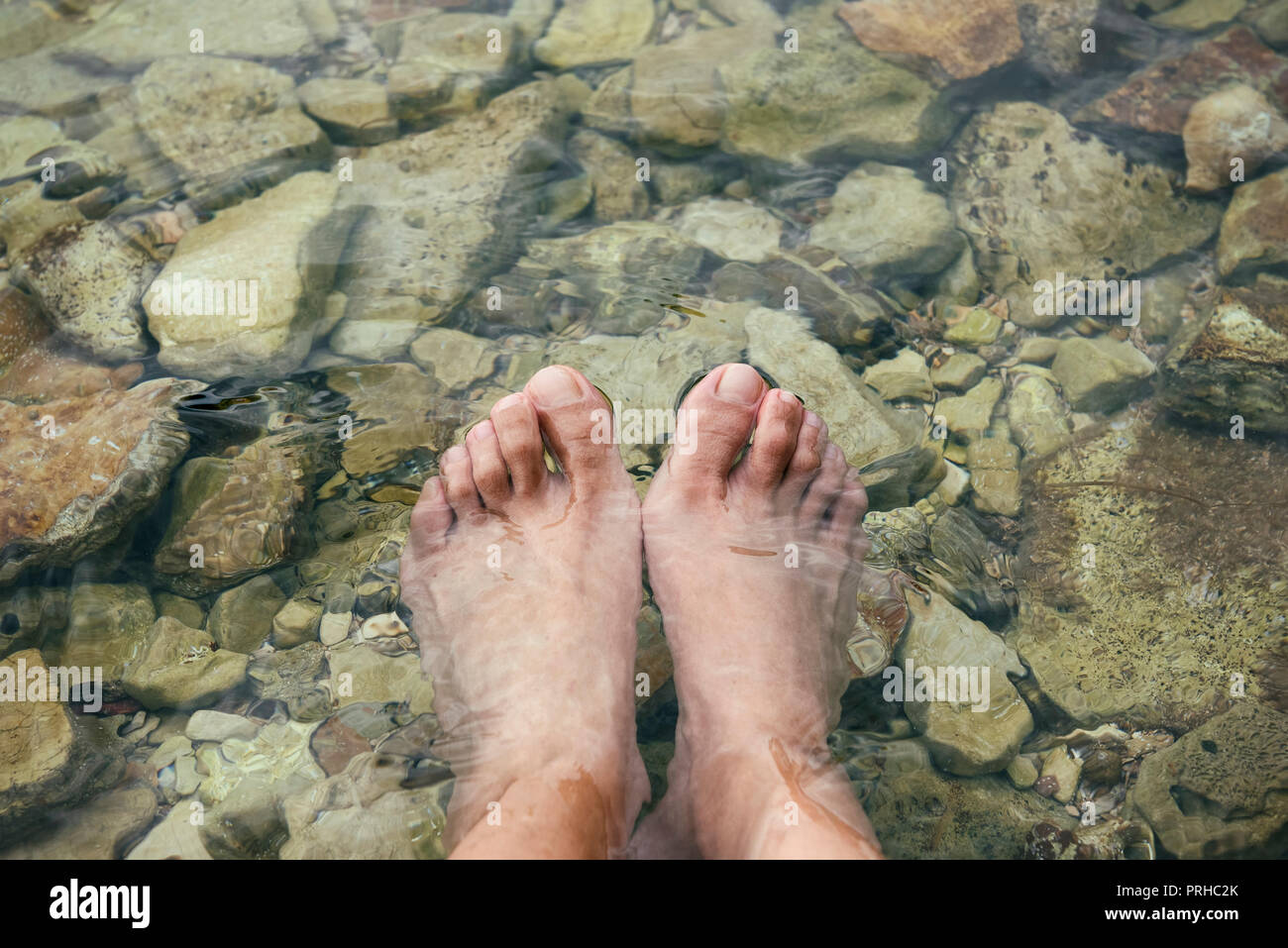 Female feet in the water (beach) - Stock Image