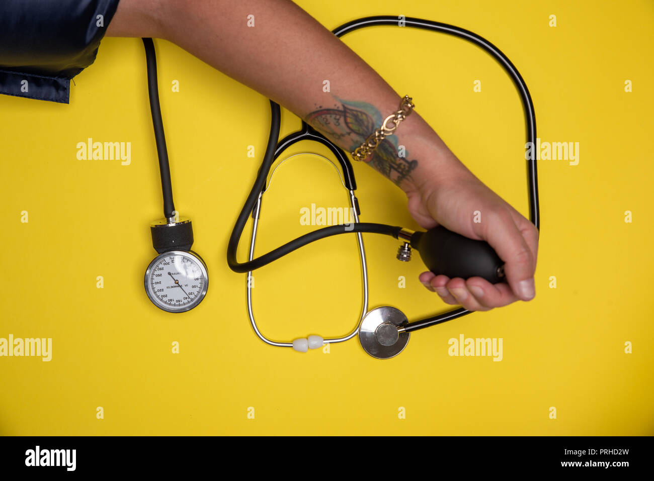 Hand checking blood pressure and stethoscope set aside. Diagnosis instruments for good heathcare - Stock Image