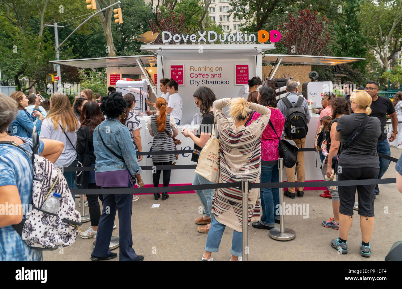 Crowds line up at the Dunkin' and Dove collaboration branding event in Flatiron Plaza in New York on Monday, October 1, 2018. Visitors were treated to free cups of coffee and samples of Unilever's Dove brand dry shampoo. Apparently, according to the organizers women run on Dunkin' and dry shampoo enabling them to quickly get up and out in the morning. Dunkin' Brands recently changed their name dropping the 'donuts' moniker to better reflect that 60 percent of their sales are coffee beverages. (© Richard B. Levine) - Stock Image