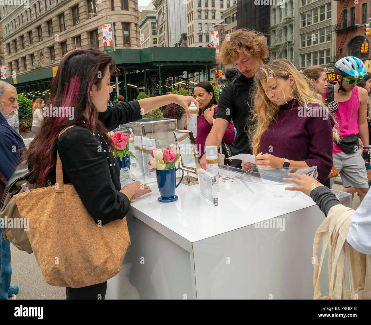 Crowds pick up sahmpoo samples at the Dunkin' and Dove collaboration branding event in Flatiron Plaza in New York on Monday, October 1, 2018. Visitors were treated to free cups of coffee and samples of Unilever's Dove brand dry shampoo. Apparently, according to the organizers women run on Dunkin' and dry shampoo enabling them to quickly get up and out in the morning. Dunkin' Brands recently changed their name dropping the 'donuts' moniker to better reflect that 60 percent of their sales are coffee beverages. (© Richard B. Levine) - Stock Image