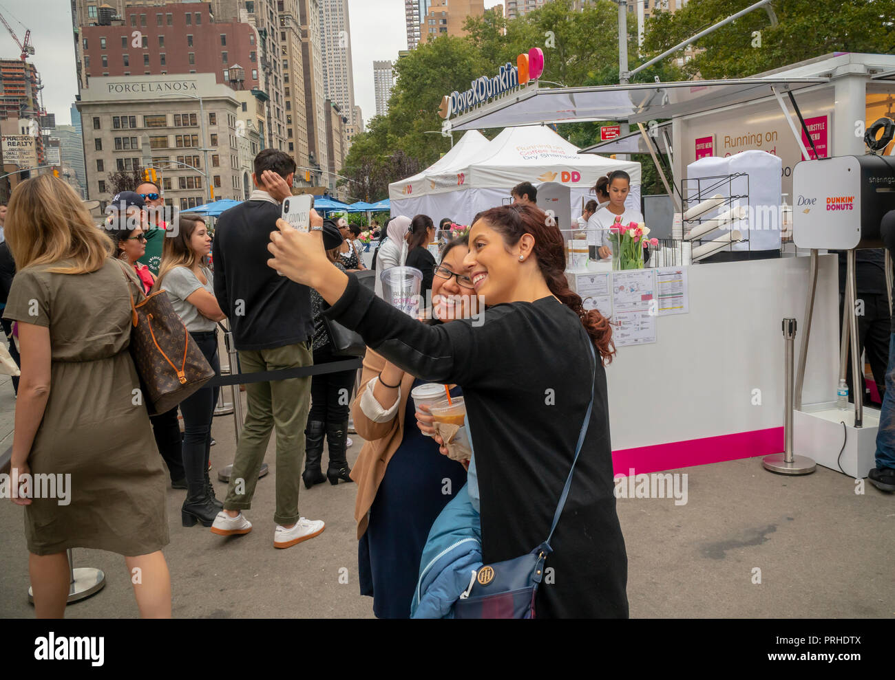 Millennials pose for a selfie at the Dunkin' and Dove collaboration branding event in Flatiron Plaza in New York on Monday, October 1, 2018. Visitors were treated to free cups of coffee and samples of Unilever's Dove brand dry shampoo. Apparently, according to the organizers women run on Dunkin' and dry shampoo enabling them to quickly get up and out in the morning. Dunkin' Brands recently changed their name dropping the 'donuts' moniker to better reflect that 60 percent of their sales are coffee beverages. (© Richard B. Levine) - Stock Image