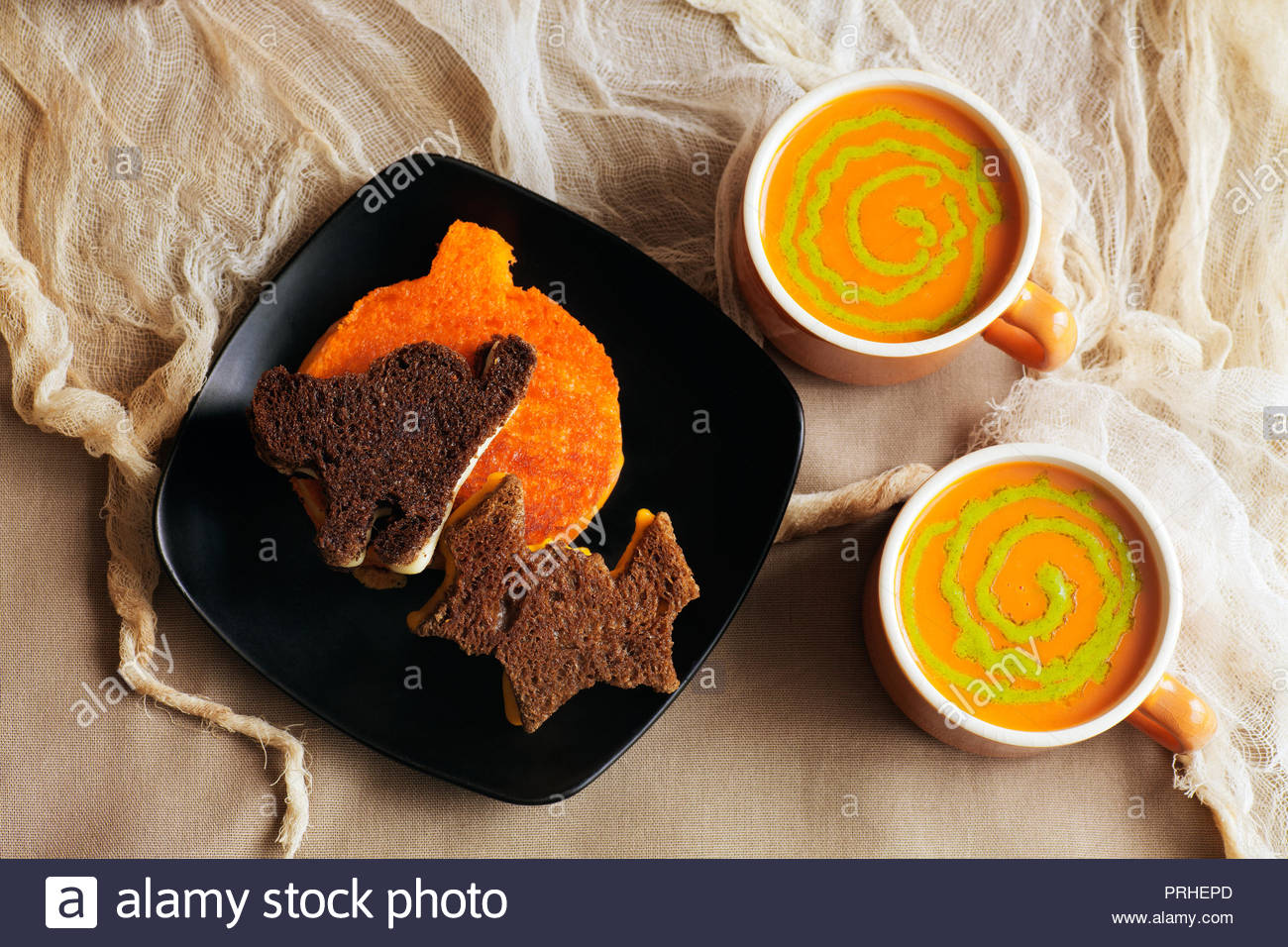 Rye, pumpernickel and ornage colored cut-out Halloween grilled cheese sandwiches. Tomato soup with pesto swirls in vintage orange cups. Shredded stain - Stock Image
